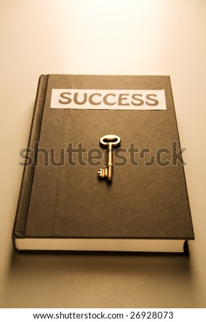 Book with 'success' label on it and the golden key too.  Warm tone.