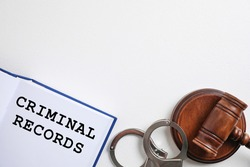 Book with words CRIMINAL RECORDS, handcuffs and gavel on white background, flat lay