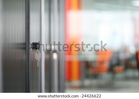 Bookcase and keys in modern office (soft focus) - stock photo