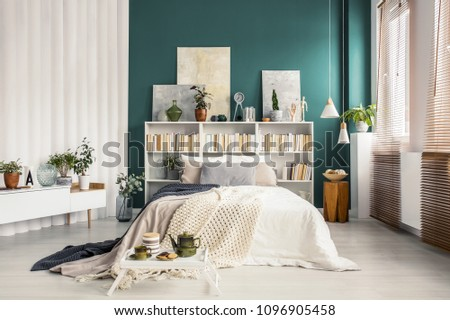 Bookcase headboard with artworks and decorations in a stylish turquoise green bedroom interior with white furniture #1096905458