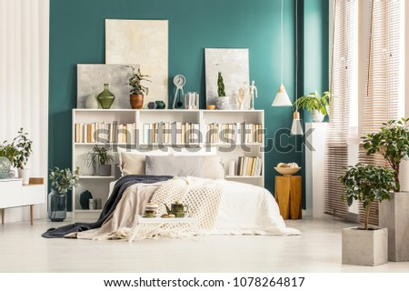 Bookcases with paintings on top standing against a dark green wall behind white bed in bright bedroom interior