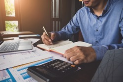 Bookkeeper accounting Concepts, Male use notebook, pen , calculator and computer laptop to working financial and budget, inspector accountant concept.