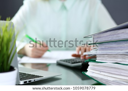 Bookkeeper or financial inspector  making report, calculating or checking balance. Binders with papers closeup. Audit and tax service concept. Green colored image background