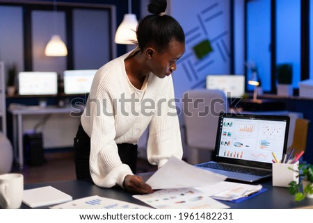 bookkeeper working on financial reports checking statistics graphs, looking at laptop, pointing to numbers standing at desk late at night in start-up office doing overtime to respect deadline.