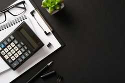Bookkeepers work place concept. Top above overhead view photo of office accessories calculator pen clipboard notebook isolated black color backdrop with blank empty space