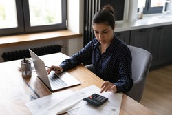 Bookkeeping. Busy millennial indian woman professional accountant preparing annual financial report checking result on calculator. Mixed race female freelancer counting tax rates declaring income