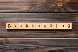 bookkeeping word written on wood block. bookkeeping text on wooden table for your desing, Top view concept.