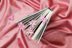 Bookmarks of fresh flowers in an open book on a pink background, top view, romantic congratulation, love emotion