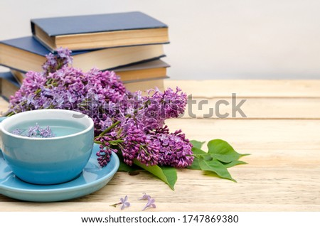 Books, a cup of blue tea from the clitoris and lilac on a wooden window. Fragrant and romantic concept. Vintage style, horizontal background, selective focus, copy space