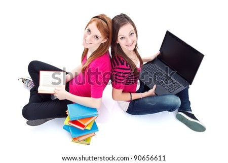 Books against computer, two girls sitting back to back