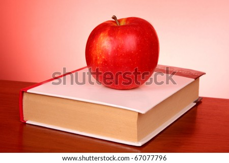 books and an apple on the red background