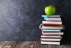 Books and apple in front of classroom chalk board. Back to school concept with copy space