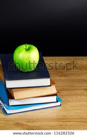 Books and apple in wood table