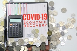 books and calculators co-written by Covid-19 Economic Recovery with a coin background