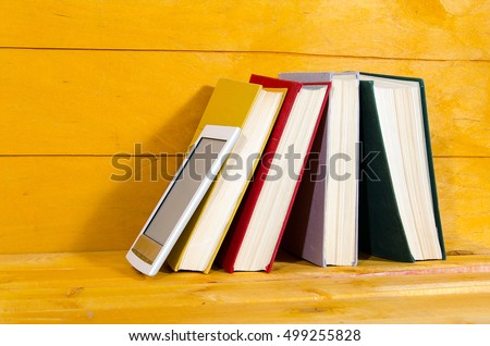Books and e-book on wooden background