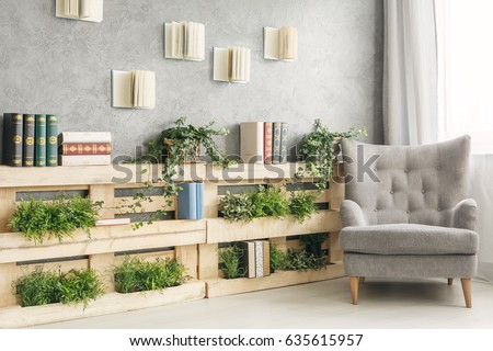 Shutterstock Books and green plants on wooden shelf in cozy lounge