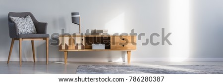Books and lamp on rustic cupboard next to grey armchair with cushion against a wall with copy space in living room interior