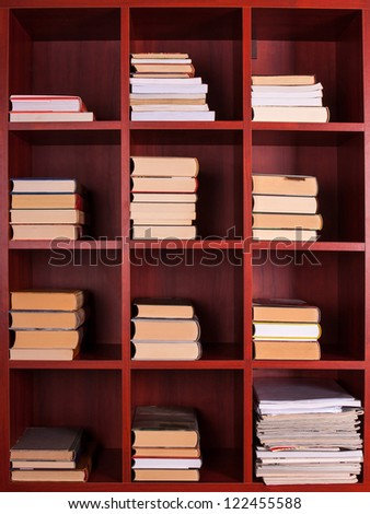 Books and magazines on a brown shelf