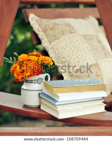 Books and marigolds in a vase stock image