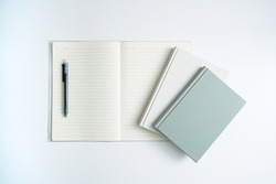 Books and open notebooks on a white desk