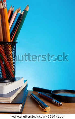 books and pen with pencil in holder basket on blue background