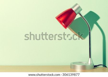 Books and red lamp on wood table.