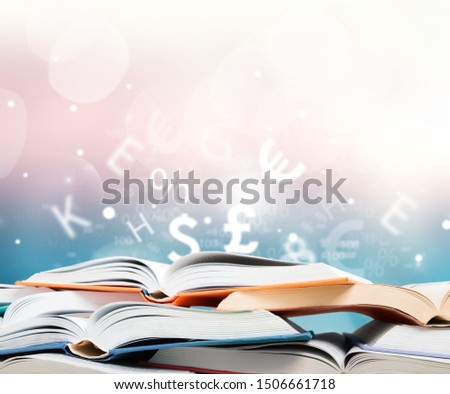 Books are opened and piled together on background