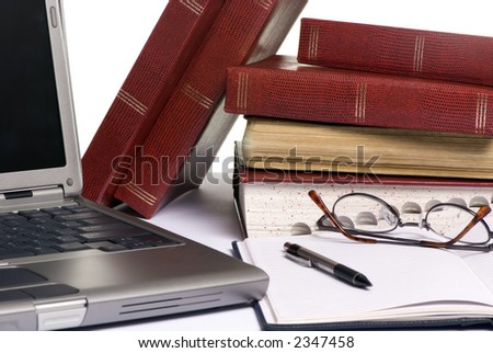 Books are strewd across a table, as somebody is doing research for an assignment paper.
