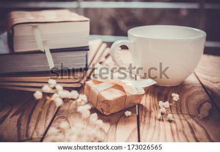 Books, flowers, white cup and wrapped gift box on wooden table. Toned image