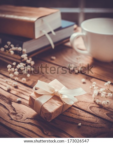 Books, flowers, white cup and wrapped gift box on wooden table. Toned picture