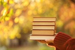 Books for the fall.Autumn book sreading.Stack of books in female hands on blurry autumn foliage in the sunshine background.Autumn time.