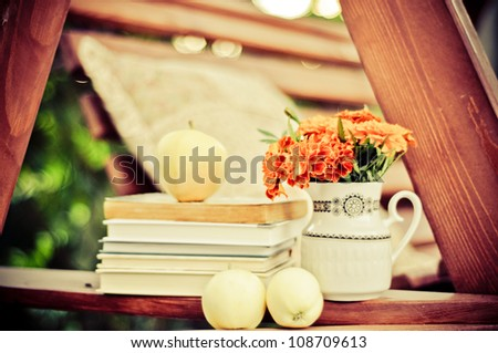 Books, fresh apples, and marigolds in a vase stock image