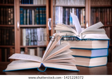 Books lie on the table against the background of bookcases. #1421228372