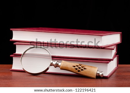 books of justice and magnifying glass on wooden table and black background