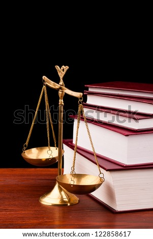 books of justice and scale on wooden table and black background