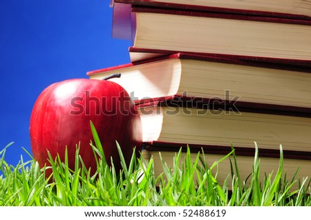 Books on grass with apple.