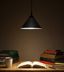 Books on wooden table under lamp light