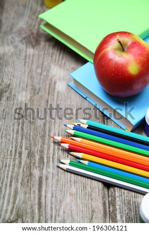 Books, pencils and an apple on a wooden background