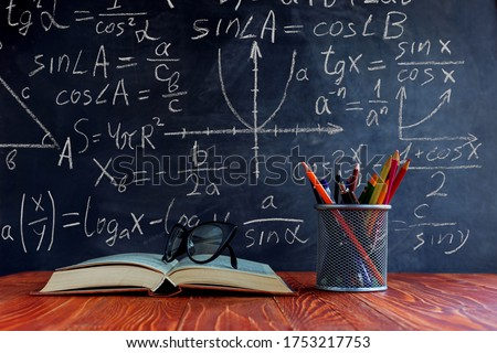 Books, pens, pencils and glasses on the table, against the background of chalkboard with mathematicsformulas. Concept, teacher's day, knowledge day. Foto d'archivio ©
