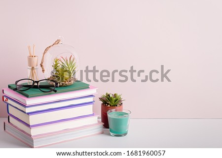 Books stack, eyeglasses, house plants succulents and fragrant candle and sticks. Background for World Book Day. Still life with stack of colorful books and home interior decor ストックフォト ©