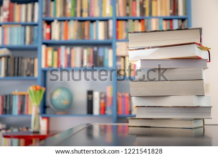 Books stacked on the table with blurred bookshelf as backdrop, A pile of books with bookshelf on the background.