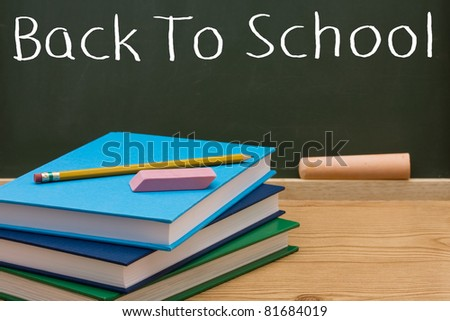 Books with a pencil and eraser in front of a chalkboard, Back to School