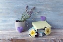 Books with bookmarks of fresh flowers, hearts, lavender bouquet on wooden table, romantic literature home reading concept