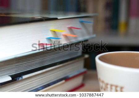 Books with bookmarks on the desk.