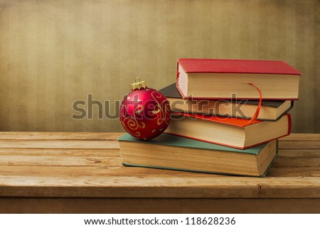 Books with christmas ornament on wooden table