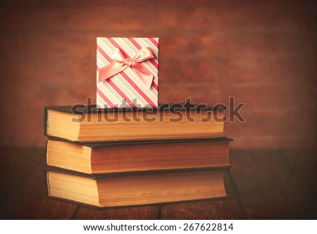 Books with gift box on wooden background. Photo in old color image style