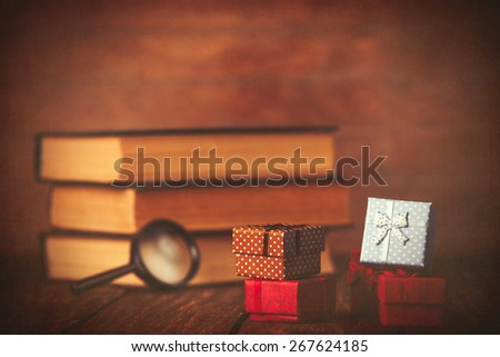 Books with loupe and gift box on wooden background.