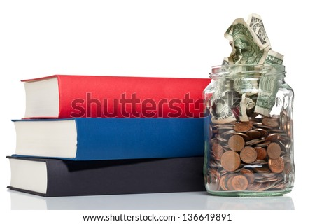 Books with penny jar filled with coins and banknotes - tuition or education financing concept