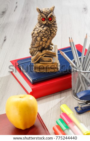 Books with statuette of owl on the top, metal stand with pencils, stapler, colored markers and notebook with yellow apple on grey wooden background. School and office work supplies