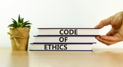 Books with text 'code of ethics' on beautiful wooden table, white background. Male hand and house plant. Business concept. Copy space.